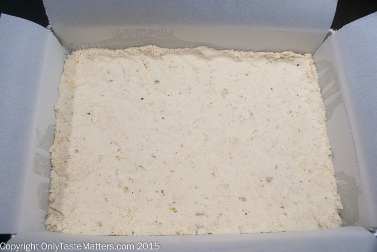 Crust for Pistachio Lemon Bars is pressed into a pan. Think cheesecake.