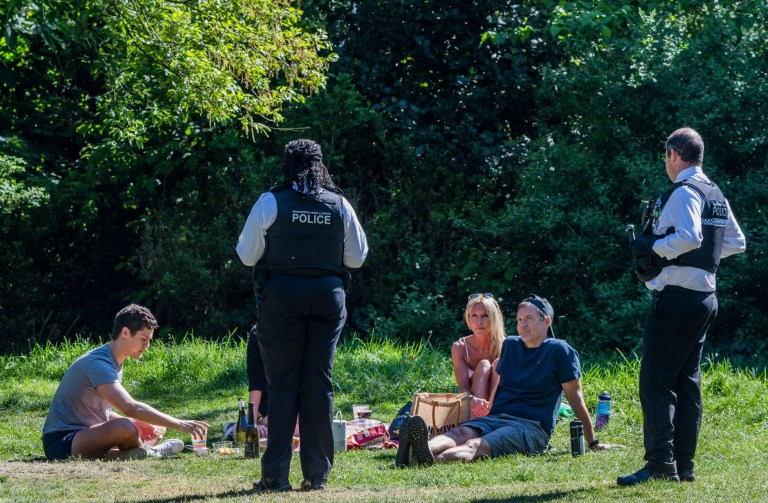A police officer speaks to people relaxing by the Serpentine in Hyde Park, London