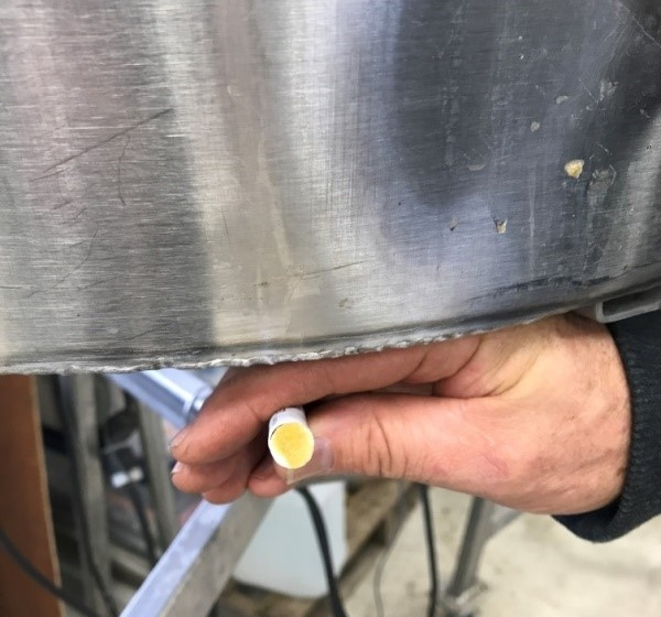 A hand holding a lead test with a yellow tip. A stainless steel container is to the top of the photo.