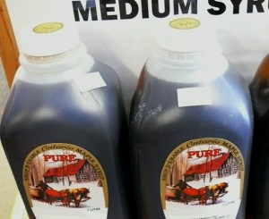 Plastic milk jugs filled with maple syrup.