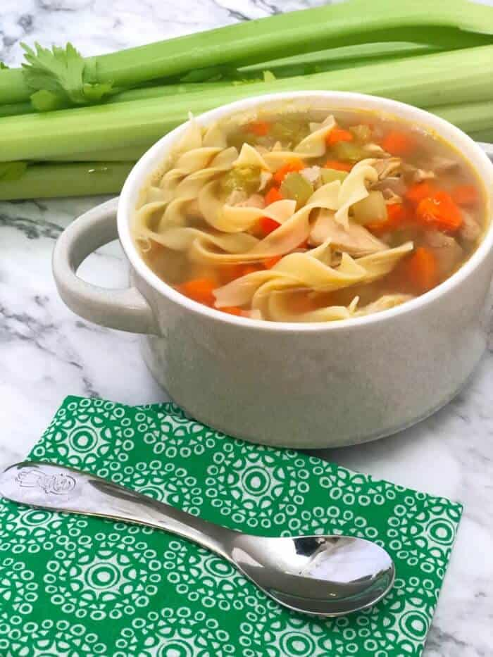 A side view of a bowl of chicken noodle soup with a napkin and a spoon