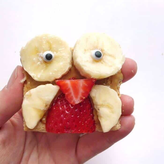 A hand holding a snack of banana slices and strawberries on a cookie shaped like an owl