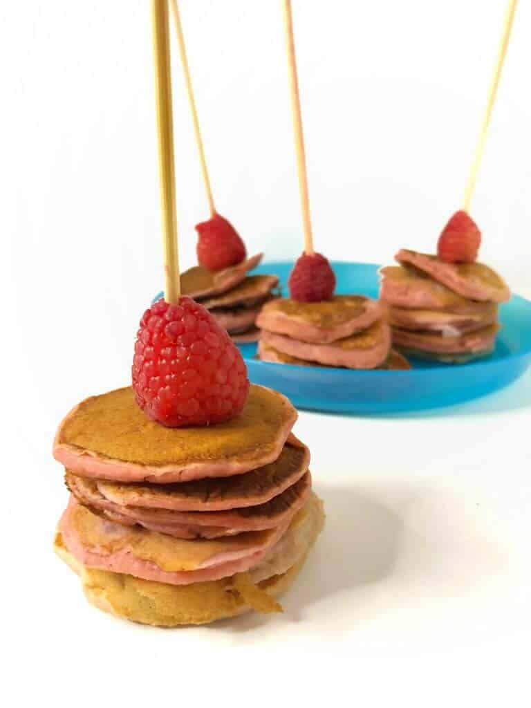 Mini pink raspberry pancakes on kabobs, one in the front, and three in the background on a plate. Each mini pancake stackis topped with a raspberry.