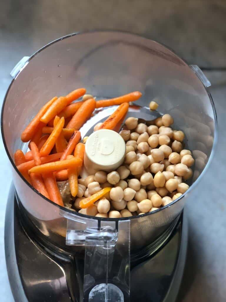 Roasted carrots and chickpeas are in a food processor from above, ready to be made into sunshine carrot veggie dip.