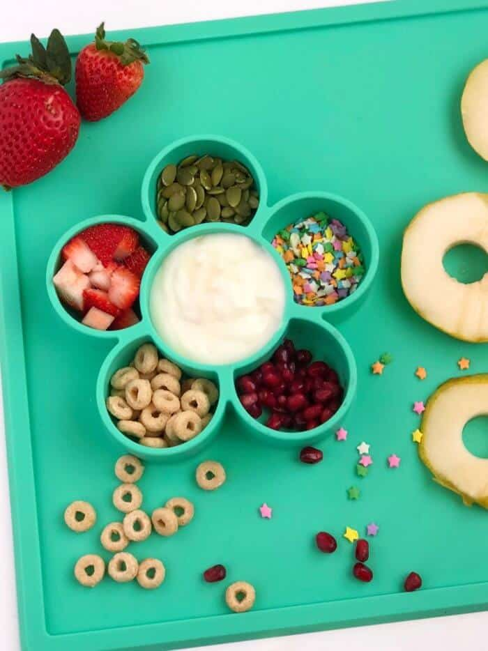 A child\'s silicone bowl shaped like a flower filled with yogurt, sprinkles, fruit and cereal