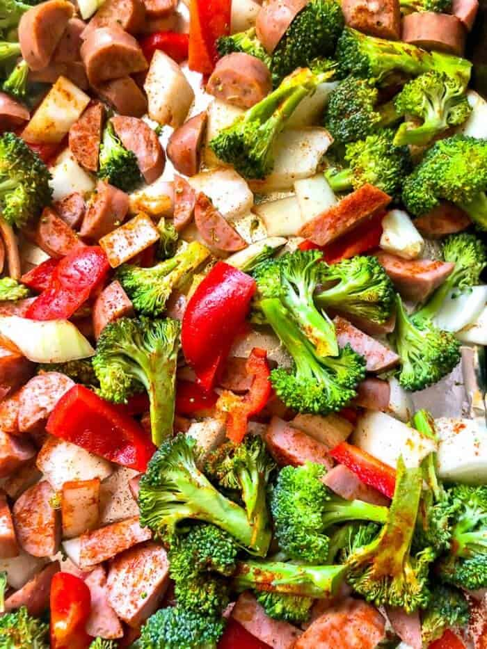 Chicken sausage pieces, broccoli and pepper scattered on a pan