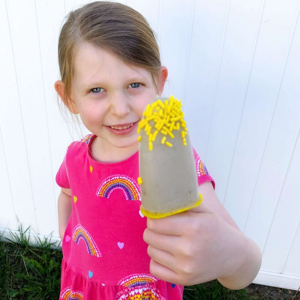A little girl holding a popsicle