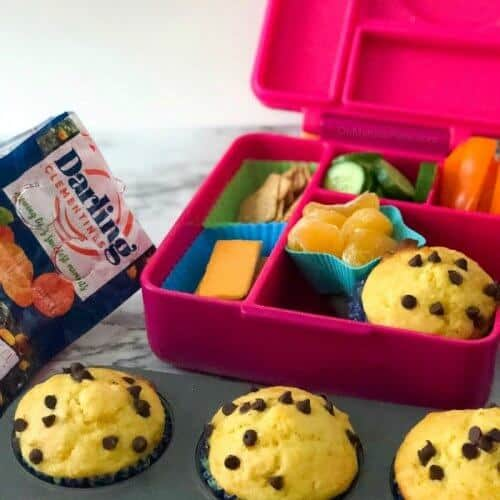 A child's lunchbox full of food with muffins in a pan in  front and a bag of clementines in the background