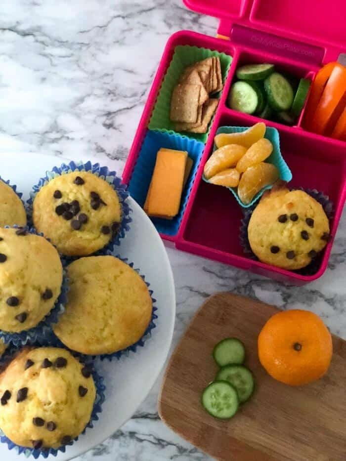 A child\'s lunchbox from overhead next to a stack of muffins and a cutting board where food is being prepped.