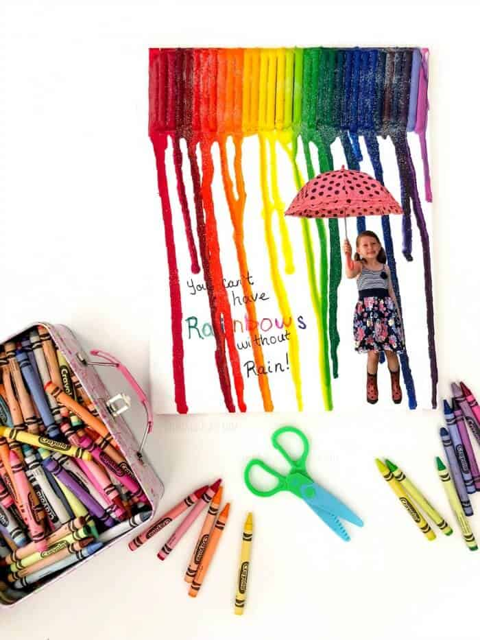Canvas with melted crayons and a girl holding and umbrella with crayons and scissors scattered around the canvas