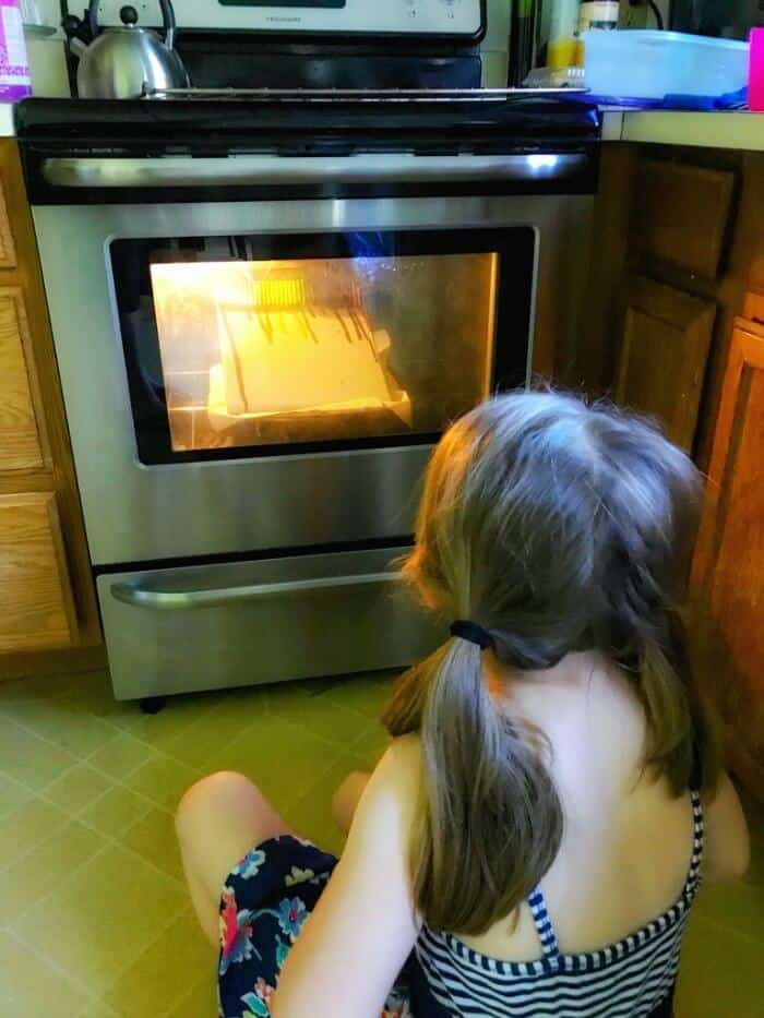 A child watching in front of an oven door