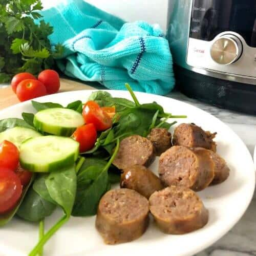 Italian sausage sliced on a plate next to a salad with an instant pot behind.