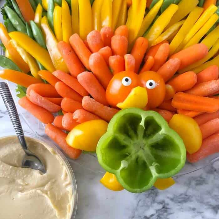 A turkey shaped vegetable platter being filled with hummus dip