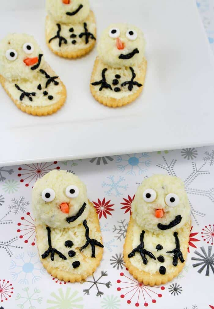 Cheese and cracker decorated to look like snowmen on a serving platter
