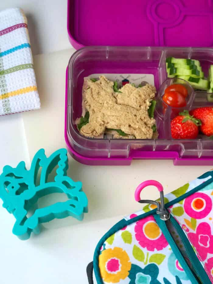 A child\'s bento lunchbox full of food including a sandwich shaped like a unicorn and a unicorn cookie cutter.