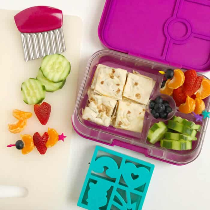 A bento lunchbox full of fruit, vegetables and a quesadilla cut into squares