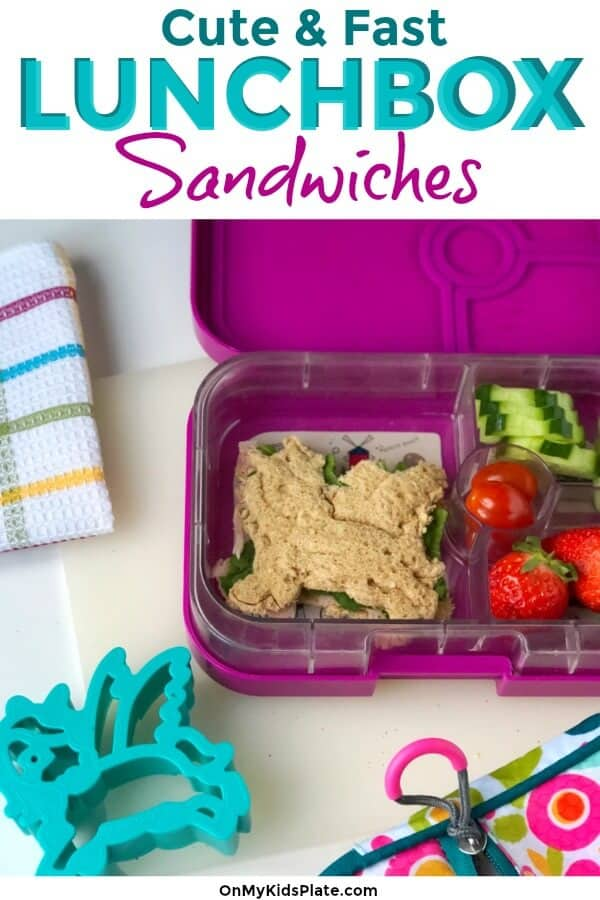 A kid\'s bento lunchbox filled with a sandwich cut out with a unicorn cookie cutter, strawberries, cherry tomatoes and cucumbers