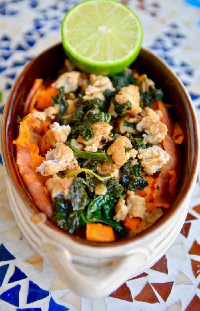 A bowl of cooked turkey, kale and sweet potatoes from above.