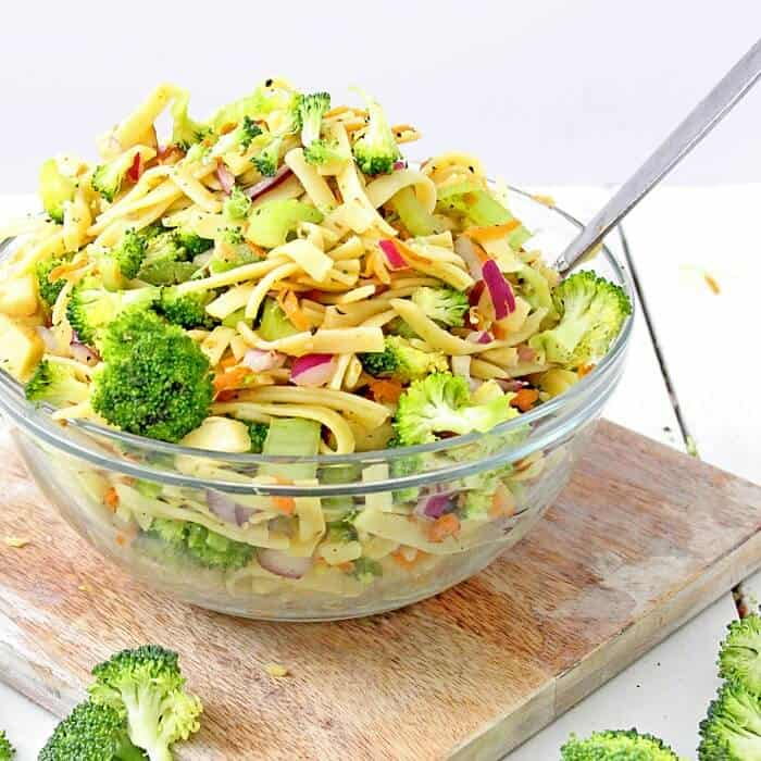 A bowl full of broccoli apple salad with pasta sits on a cutting board coated in a lightly tangy apple cider vinegar and yogurt dressing.