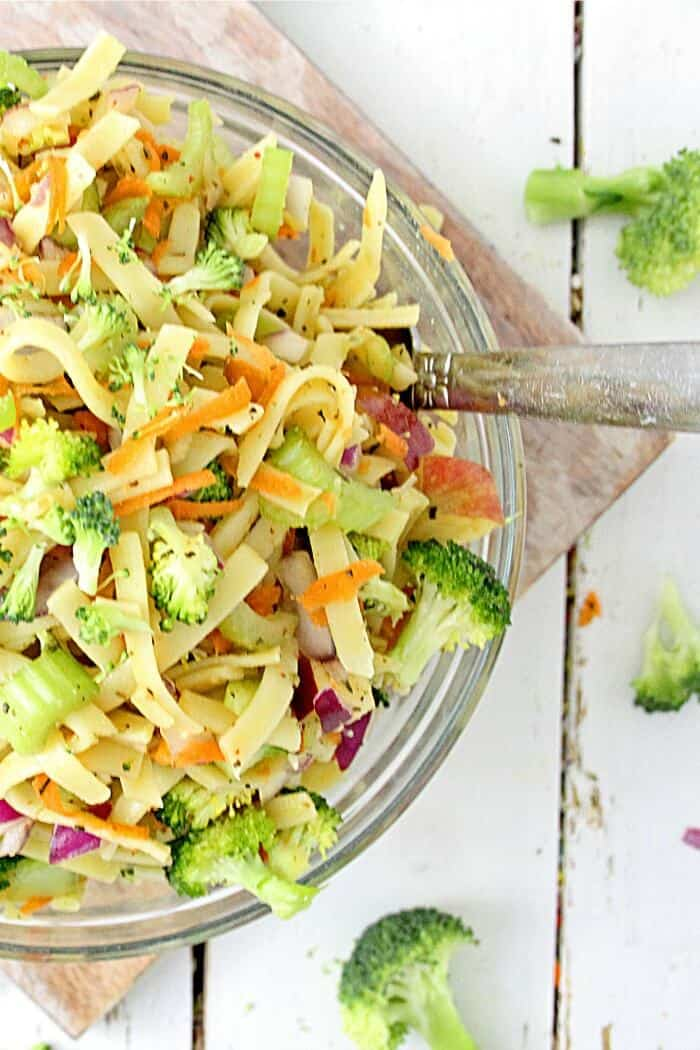 A bowl of pasta, broccoli, shredded carrots, cabbage and celery from overhead.