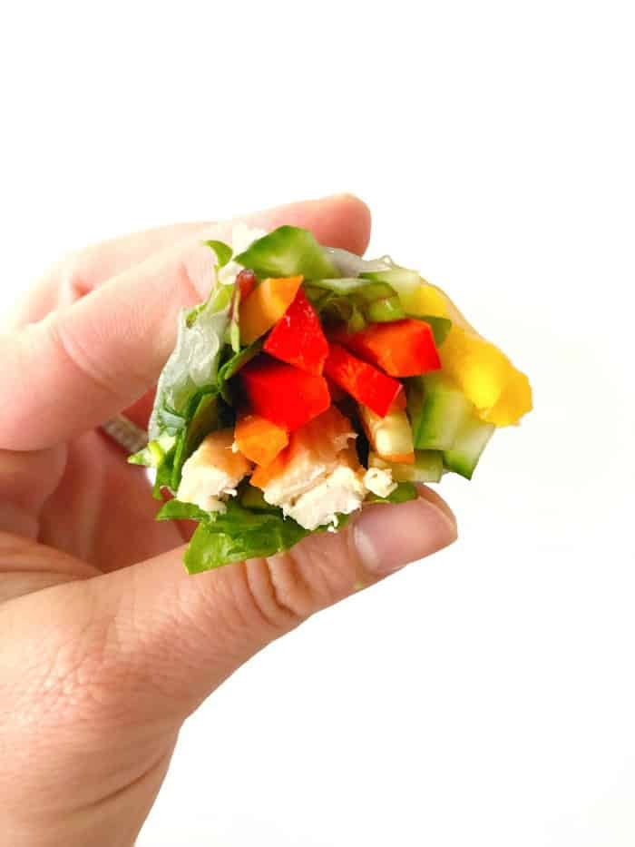 The inside after a bite of a fresh spring roll with bell pepper, mango, chicken, and greens being held by a hand.