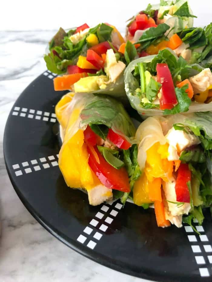 A plate of fresh spring rolls cut in half full of mango, pepper, chicken and spinach