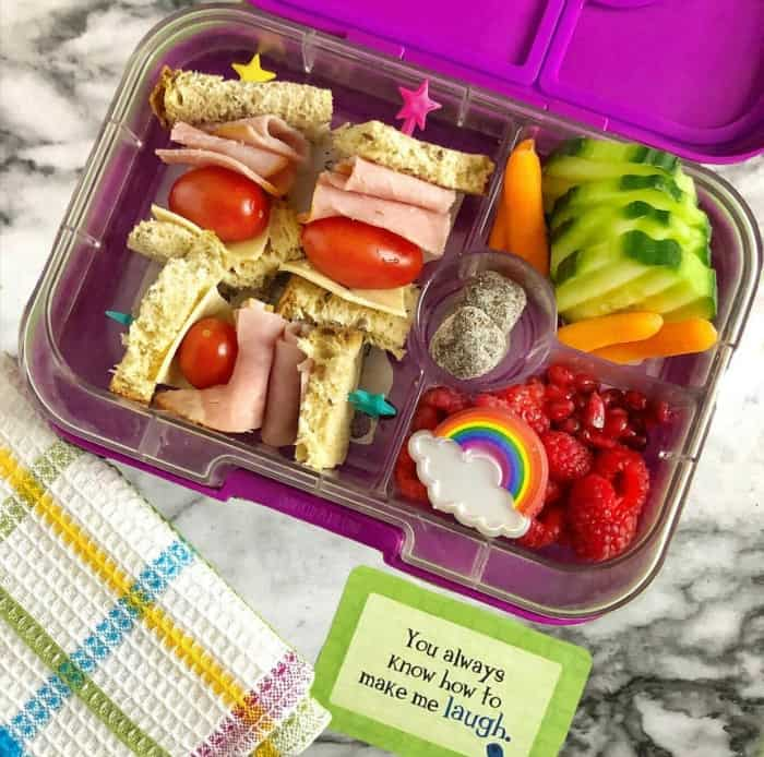 A kid\'s bento lunchbox full of a ham sandwich and cherry tomatoes cut into bites on skewers, cucumbers, raspberries, pomegranate seeds, carrots and  a rainbow.