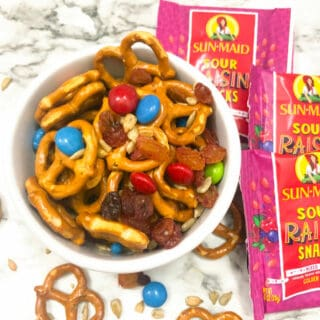 Pretzels, raisings and chocolate pieces in a bowl next to pouches of raisins