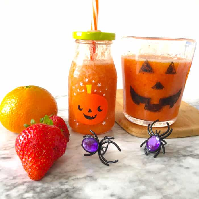 orange smoothie in a cup and milk glass decorated like pumpkins next to fruit and spider rings