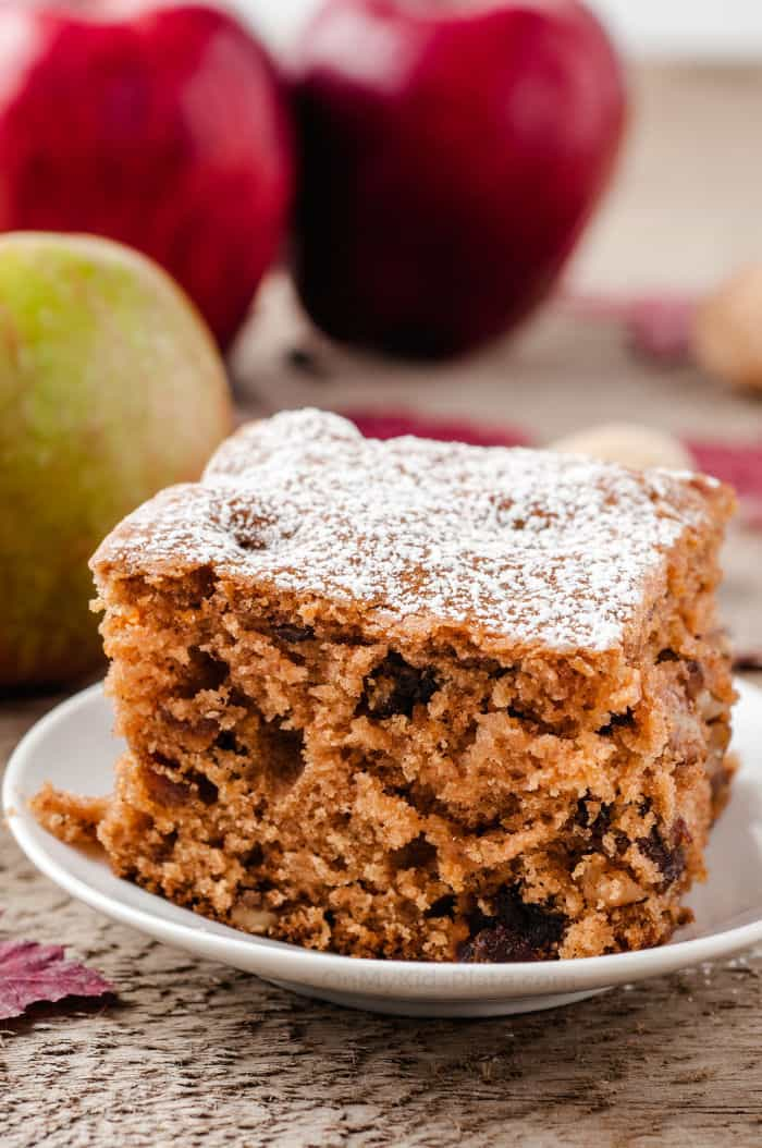 A slice of apple walnut cake sits on a plate with apples in the background.