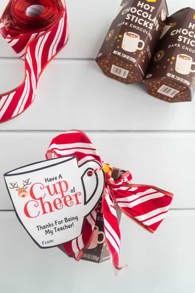 """A hot chocolate gift  being put together dressed up with a ribbon and a reindeer on a mug shaped gift tag that says \""""cup of cheer, thanks for being my teacher\"""""""