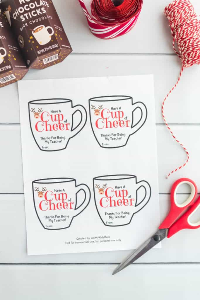 """Mug shaped gift cards on a piece of paper that say \""""Have a cup of cheer, thanks for being my teacher\"""" with a reindeer on them. Scissors and red string are also in the frame."""