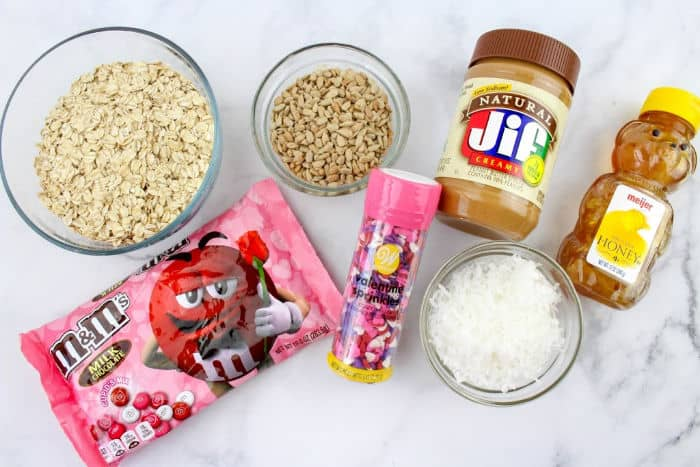 Jar of peanut butter, coconut, sprinkles, bag of chocolate candies, oats and honey from overhead