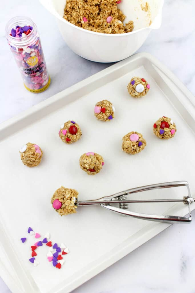 No bake snack bites being scooped and placed on a baking sheet.