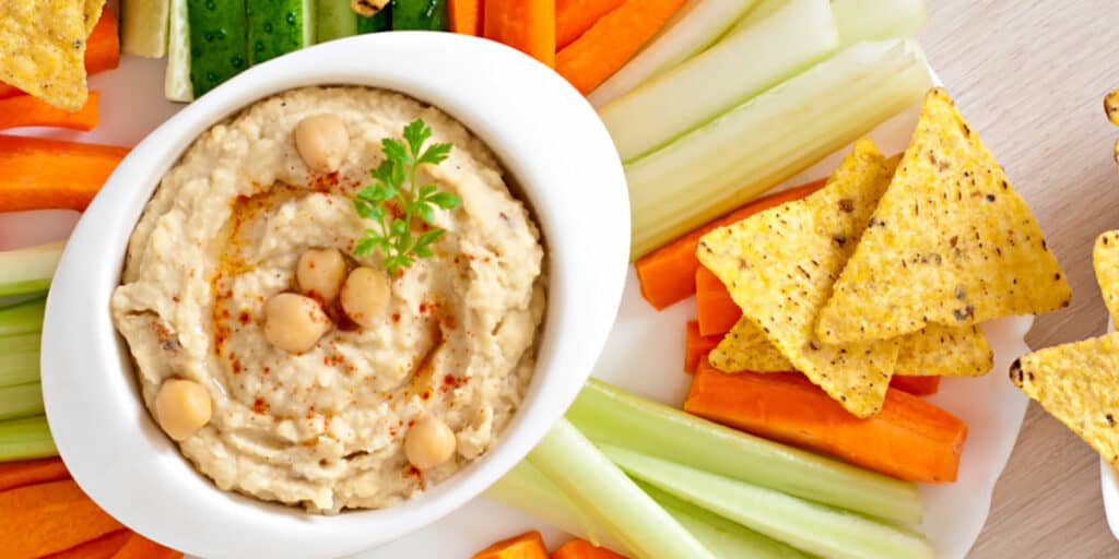 A tray of hummus with vegetables and chips