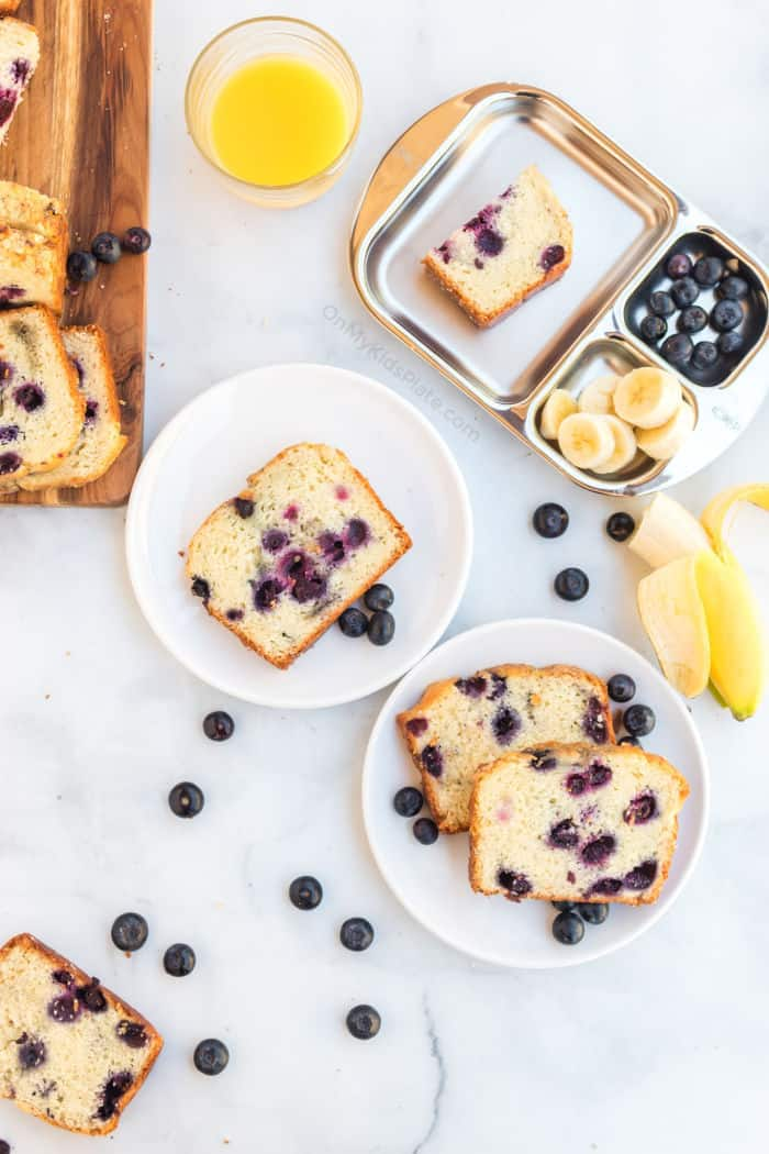Blueberry bread slices being served on plates and a kids tray plate with fresh fruit