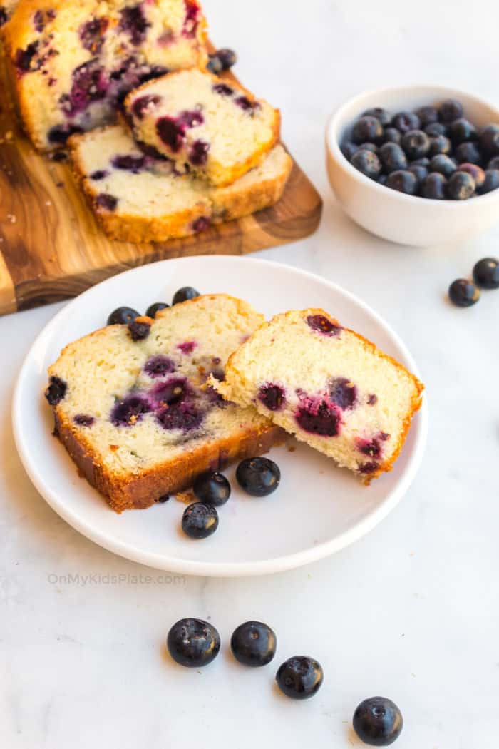 A piece of blueberry cake on a plate with more slices on a cutting board