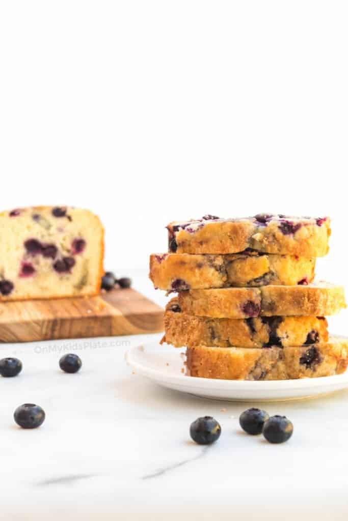Blueberry bread sliced stacked high on a plate with more slices on a cutting board