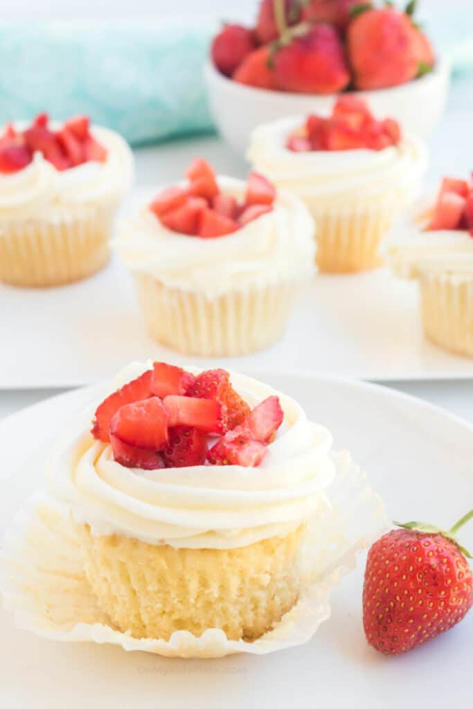 A close-up of a cupcake with frosting and fresh diced strawberries being unwrapped, with more cupcakes on a plate behind.