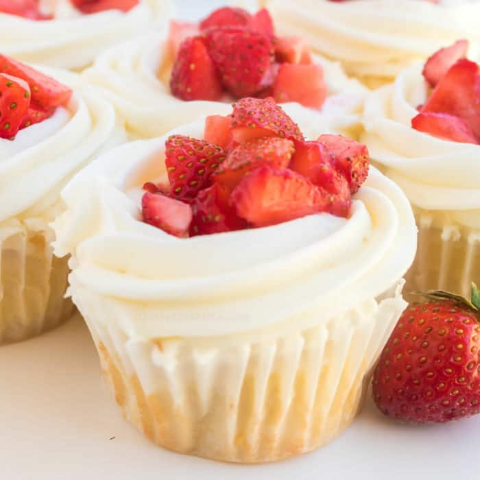 A cupcake with frosting and fresh strawberry pieces on top