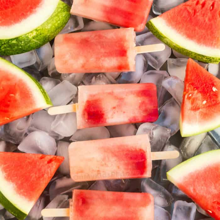 A close up view of watermelon Popsciles and slices of watermelon on a tray full of ice.