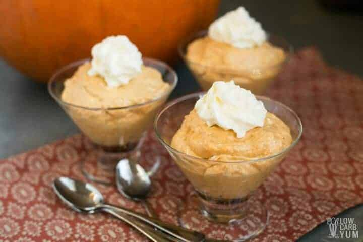 Orange mousse in three bowls with whipped cream