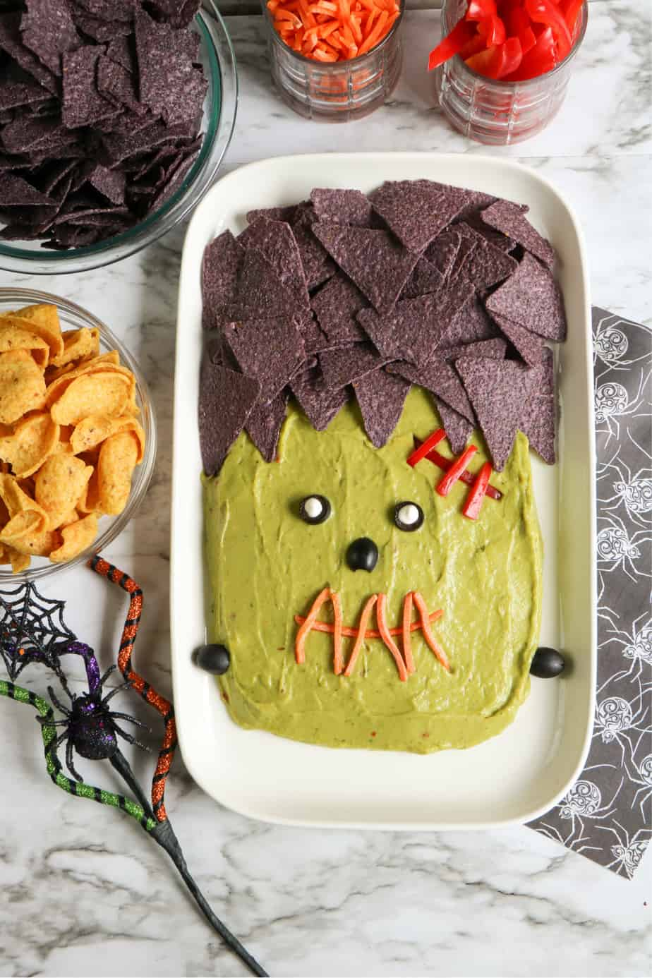 Plater of guacamole decorated to look like Frankenstein with jars of chips and veggies to dip in bowls