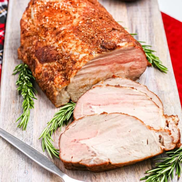Close up of sliced pork loin on a serving platter with rosemary.
