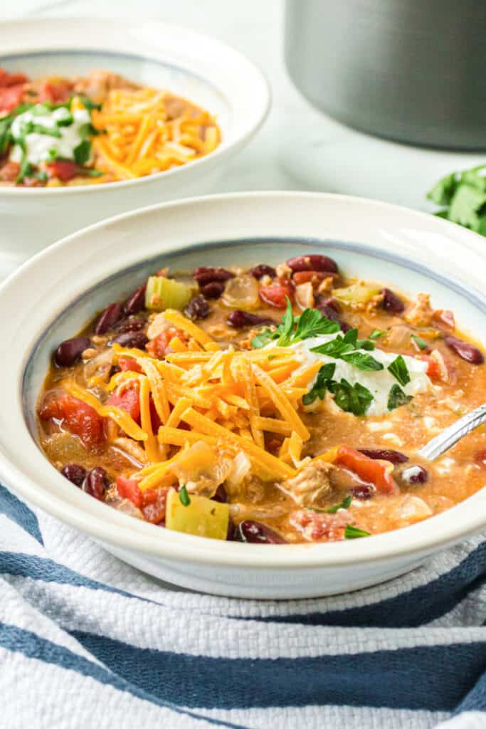 Looking over a of a bowl of turkey chili topped with cheese and sour cream.