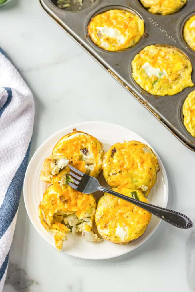 Egg bites on a plate with a fork, a muffin pan with baked omelets insider to the side.