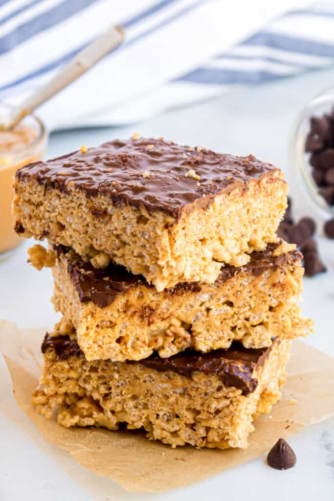 Three rice krispie treats topped with chocolate stacked with peanut butter and chocolate chips in the background