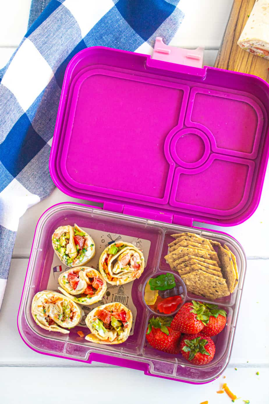 A child's lunchbox full of vegetable cheese pinwheels, strawberries, crackers and gummy bears.
