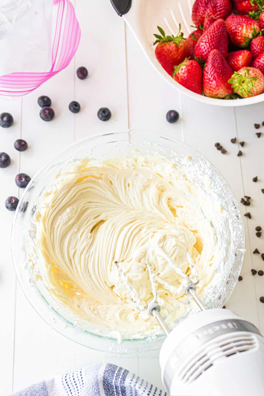 Cream cheese filling being whipped in a bowl with a hand mixer.