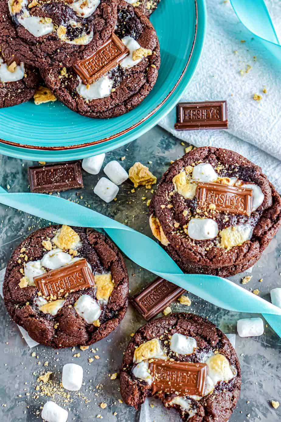 chocolate marshamllow smores cookies on a plate and on a table, one cookie with a bite.